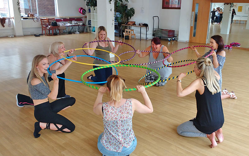 Seven girls with hula hoops in a gym