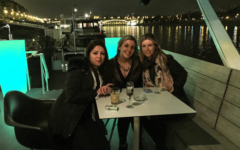Three girls drinking on the decks of a boat on the River Danube