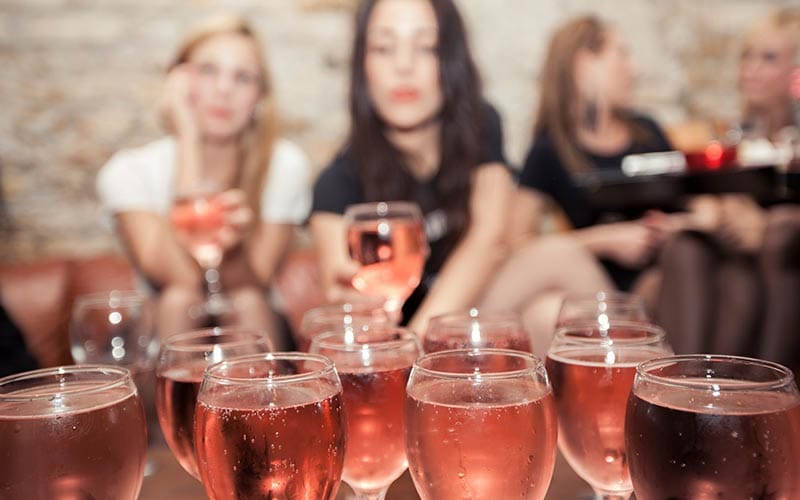 Some glasses of rose in focus in the foreground and some blurred girls in the background