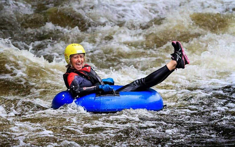 A woman on a rubber ring, floating down the rapids