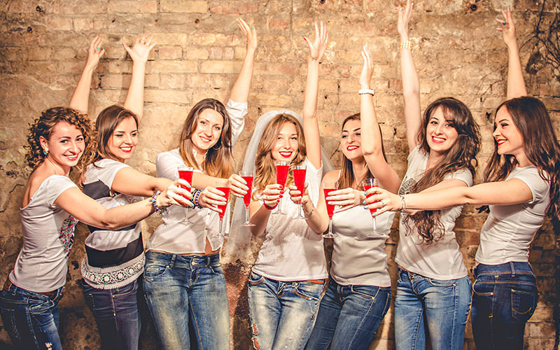 A group of girls wearing white T-shirts and jeans, holding glasses of red alcohol in their hands