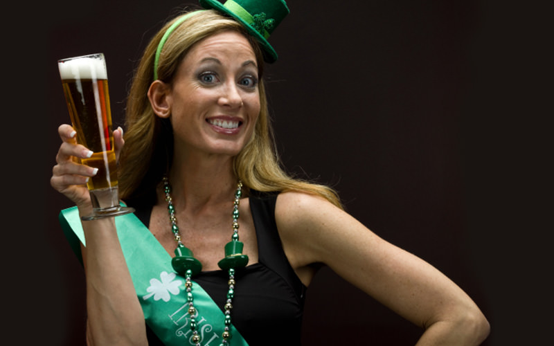 A woman wearing an Irish themed hat, with a green sash on, holding a pint