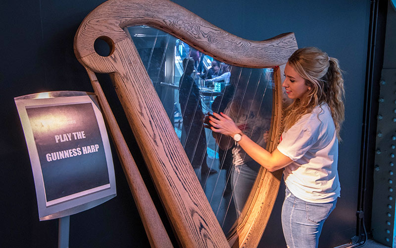A girl playing the harp in The Guinness Factory, Dublin