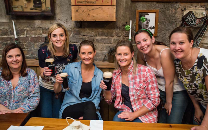 Some girls on a night out holding pints of Guinness