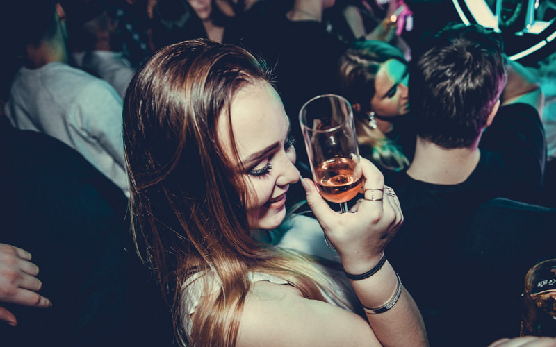 A woman holding a prosecco flute in a club