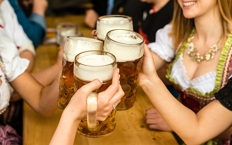 Some people holding steins up in a Bavarian beer hall