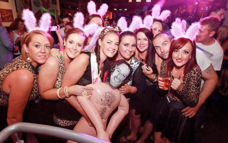A group of hens with a blow up inflatable man