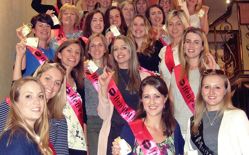 A group of girls all wearing hen party sashes and standing on stairs