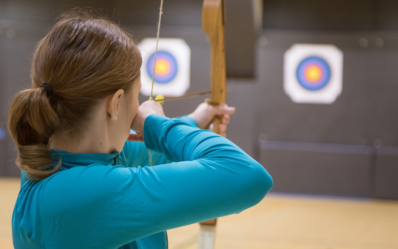 A girl aiming an arrow at a target board