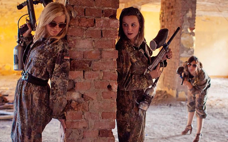 Three girls wearing army overalls, with paintball guns