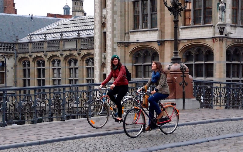 Two girls cycling in Lisbon, along a bridge