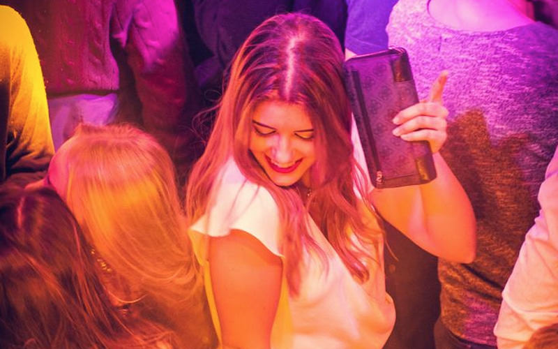 A girl dancing in a club, holding her purse