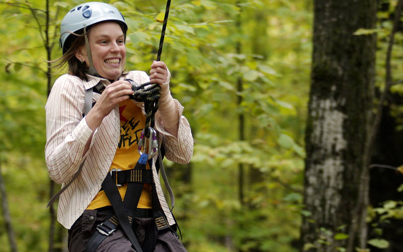 A girl doing a zipwire through the trees