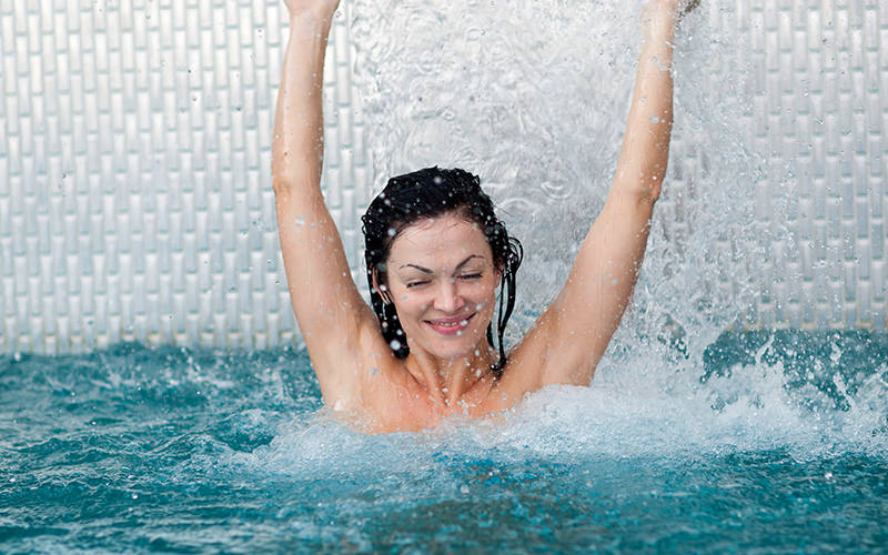 A girl in the swimming pool, standing under a waterfall water feature
