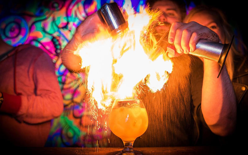 A barman making a flaming cocktail