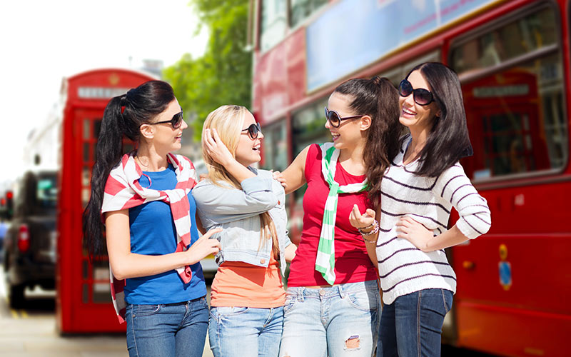 Four girls standing in front of a London bus