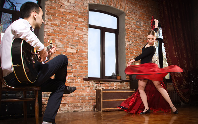 A woman flamenco dancing whilst a man plays the guitar