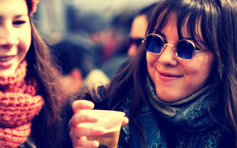 A girl wearing sunglasses and carrying a small beer