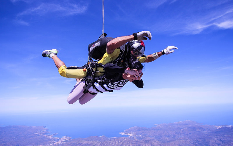 A woman doing a tandem skydive with an instructor
