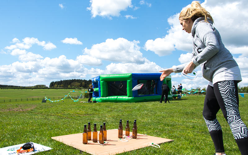A girl throwing a hoop around some bottles in Geordie Games