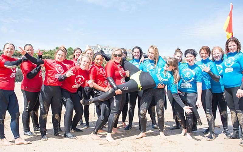 A large group of girls wearing wetsuits in Newquay