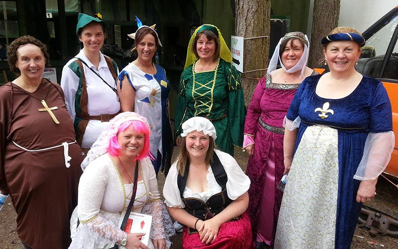 Eight women in Sherwood Forest themed fancy dress outfits