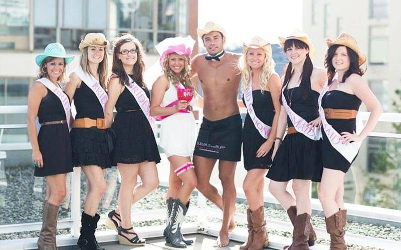 Seven girls wearing cowboy outfits with a topless stripper in the middle