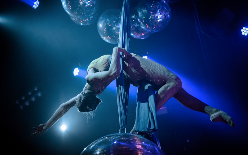 A dancer suspended from the ceiling, with balloons above her