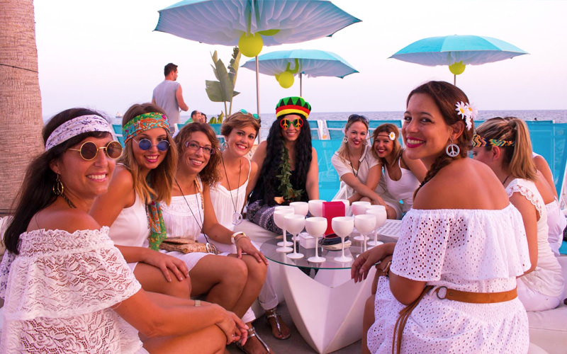 Some girls dressed all in white, in fancy dress as hippies on their Palma hen weekend