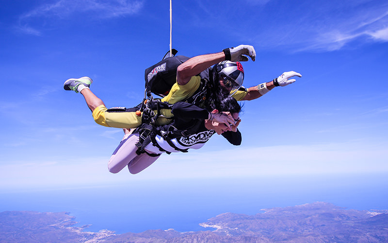 Two people sky diving, with a rope attached to them