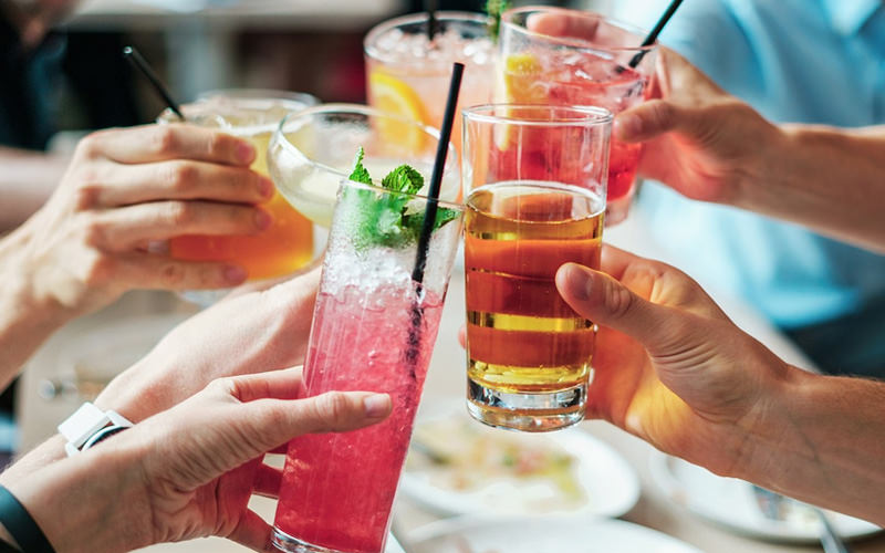 A close up of peoples hands holding various cocktails and drinks