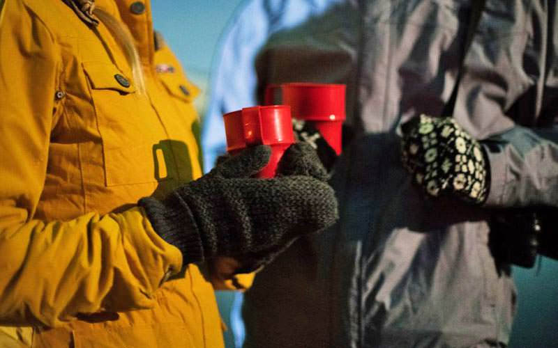 A close up of two people in coats and mittens, holding red mugs