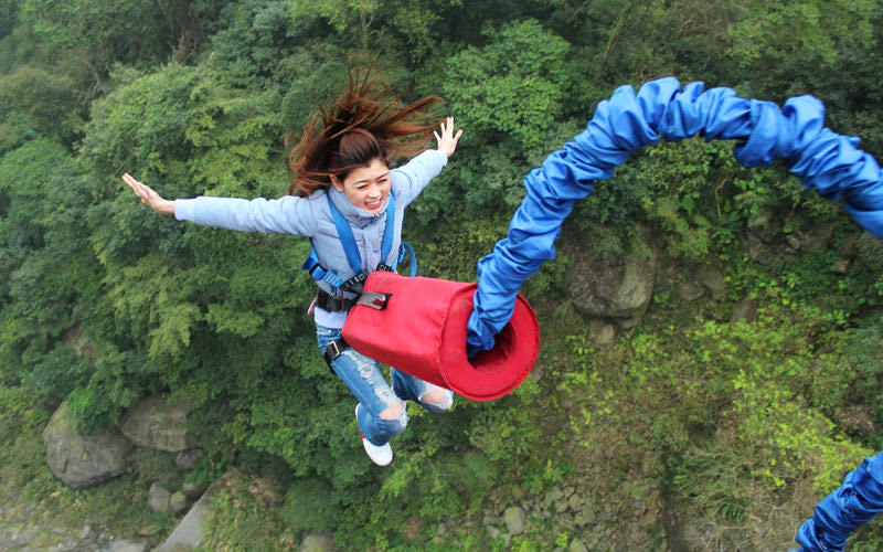 A girl hanging off the edge of a bungy cord