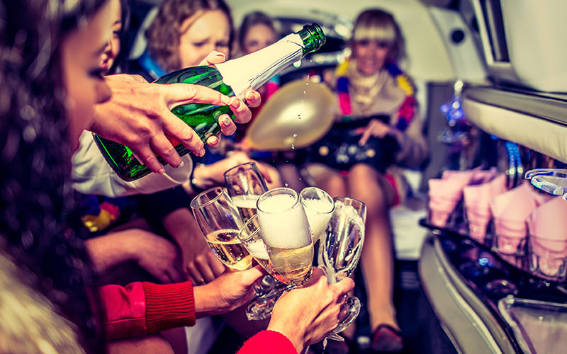 A group of girls in a party limo, pouring drinks