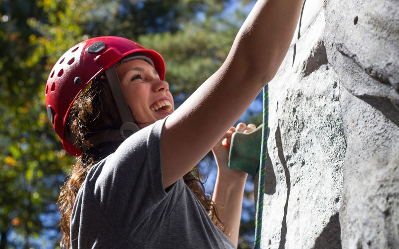 A girl wearing a helmet, climbing a wall outside