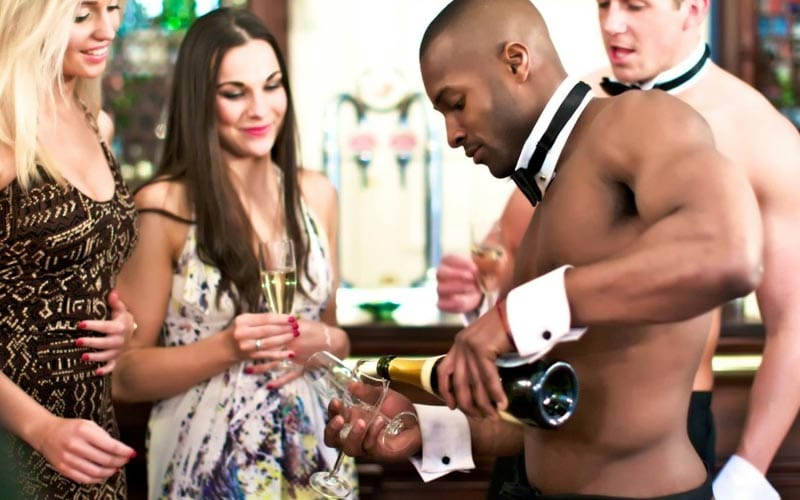 A topless waiter pouring a drink into a champagne glass, with two women next to him