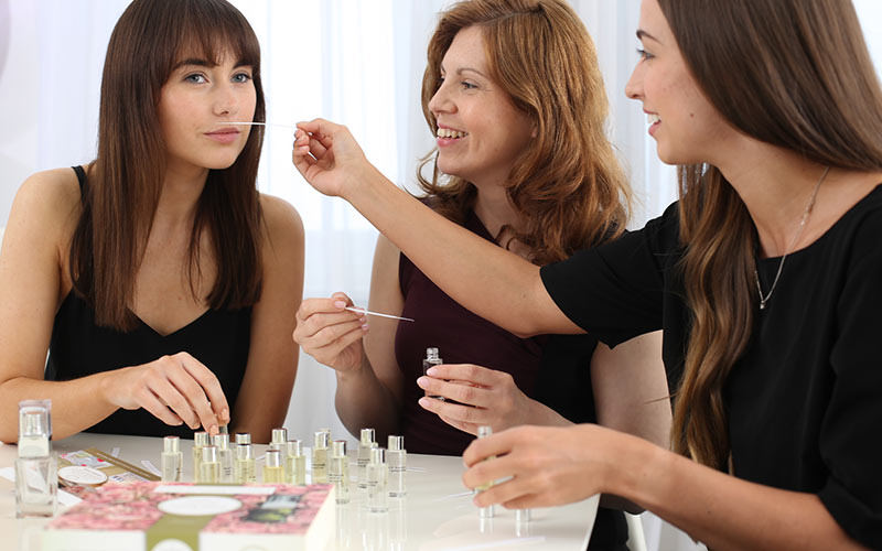 Three women smelling various perfumes on a table