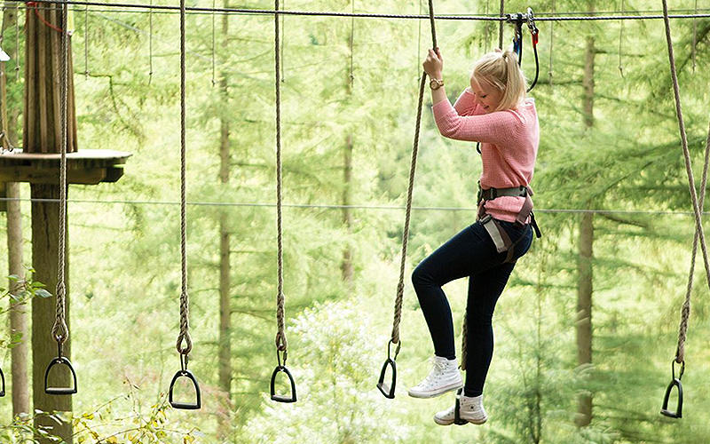 A girl on high ropes, in a harness