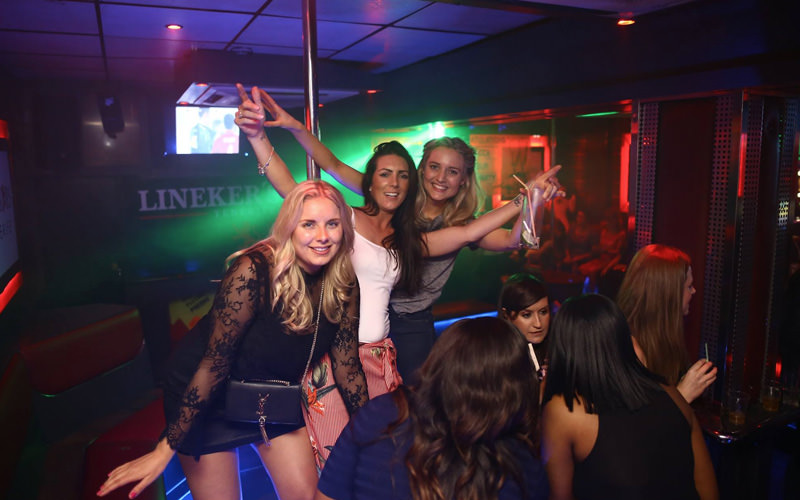 A group of girls in a club, posing around a pole