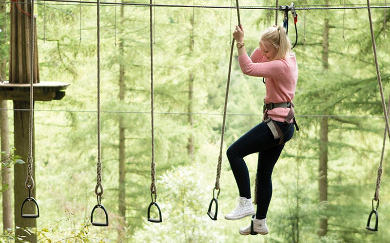 A girl in a harness on some high ropes