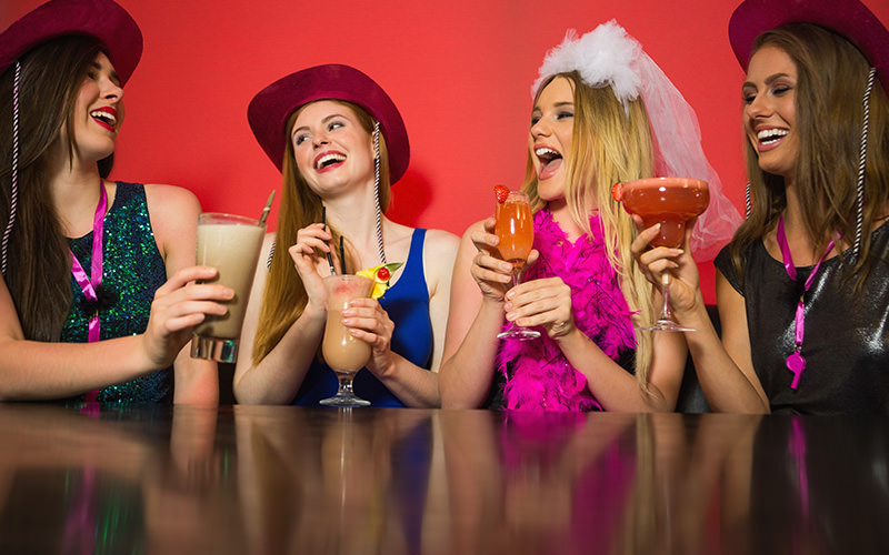 Four women sat around a table, drinking cocktails