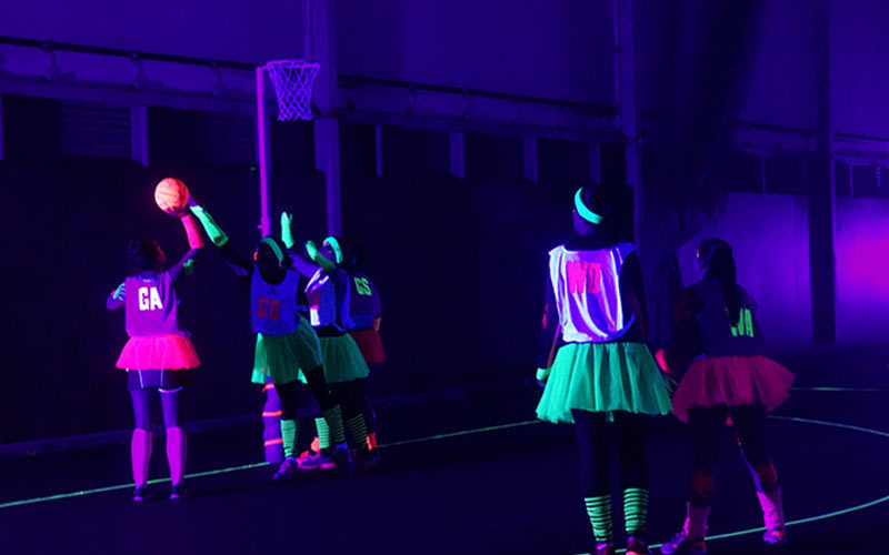 A group of women playing netball in the dark, wearing glow in the dark clothes