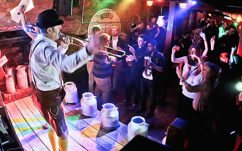 A group of people dancing and a man playing a trumpet, stood on a table