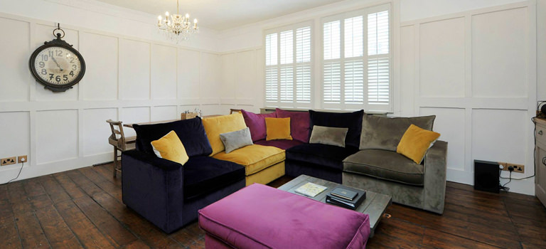 A lounge area with colourful sofas