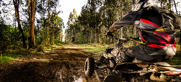A quad bike travelling through the mud