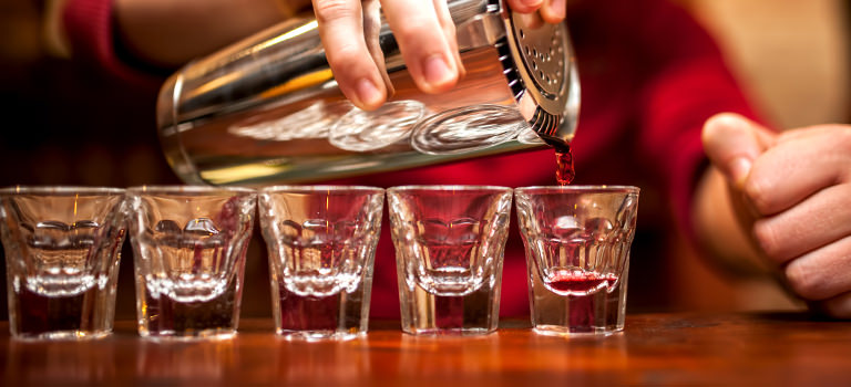 A barman pouring shots into shot glasses