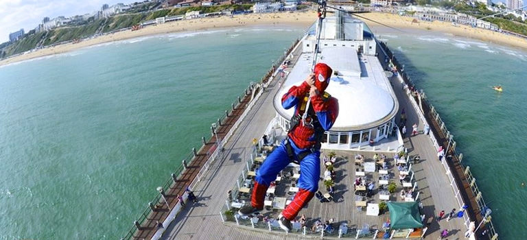 A man dressed as Spiderman ziplining off the pier