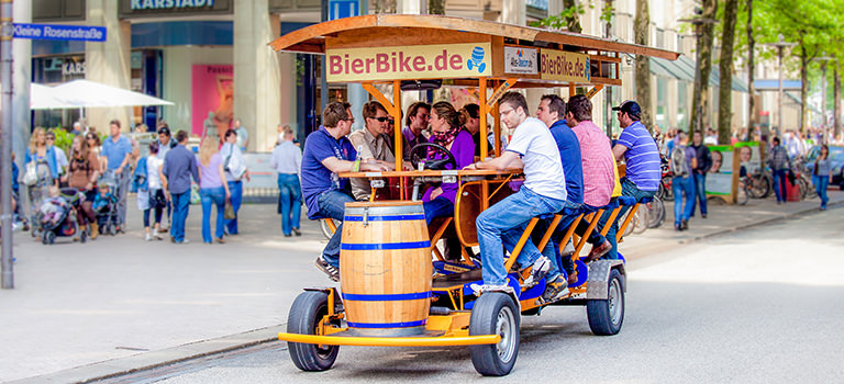 A group of men riding a beer bike