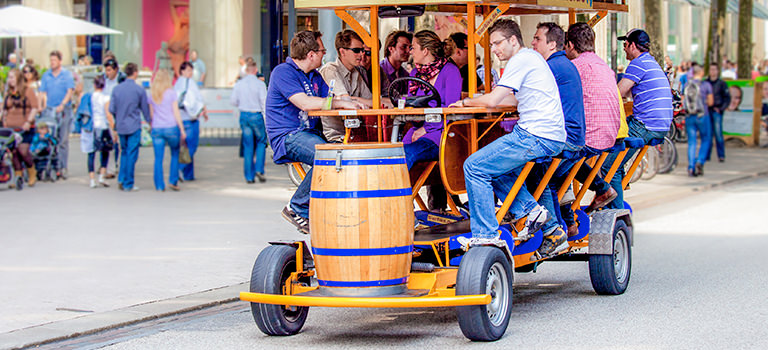 A group of young men riding a yellow and blue beer bike. They sit at a table as the man cycles. At the back is a large beer barrel.
