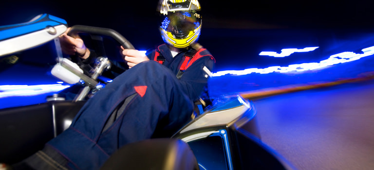 Colourful picture of a man wearing a crash helmet and driving gear while driving a go cart at high speeds